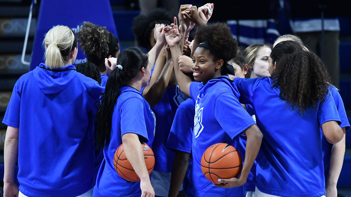 Members of the women's basketball Billikens celebrate together.
